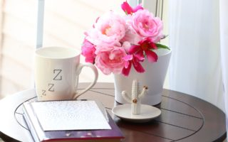 Coffee mug with flowers and notebook on a table - sample